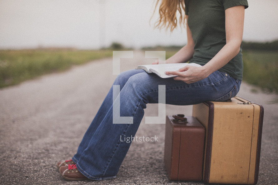 Woman reading a Bible while sitting on a suitcase in the middle of a dirt road.