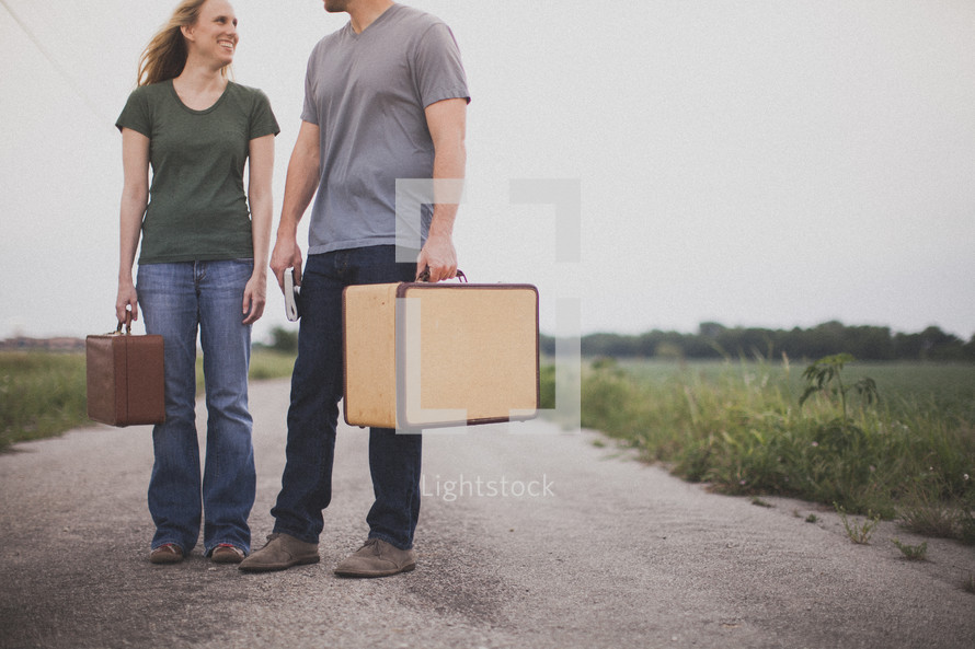 man and woman carrying luggage standing in the middle of a road