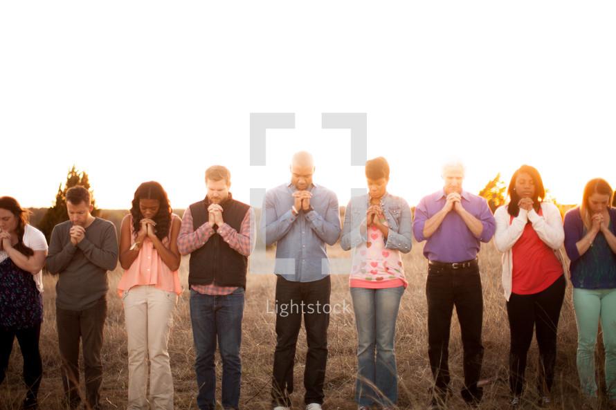 group, prayer, praying hands, heads bowed, man, woman, African American, outdoors