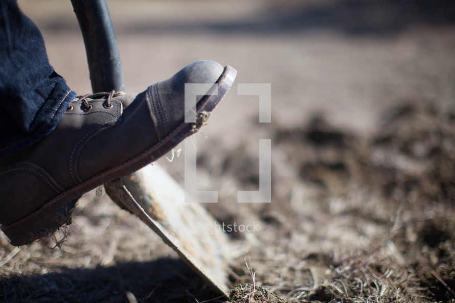 foot on a shovel breaking ground