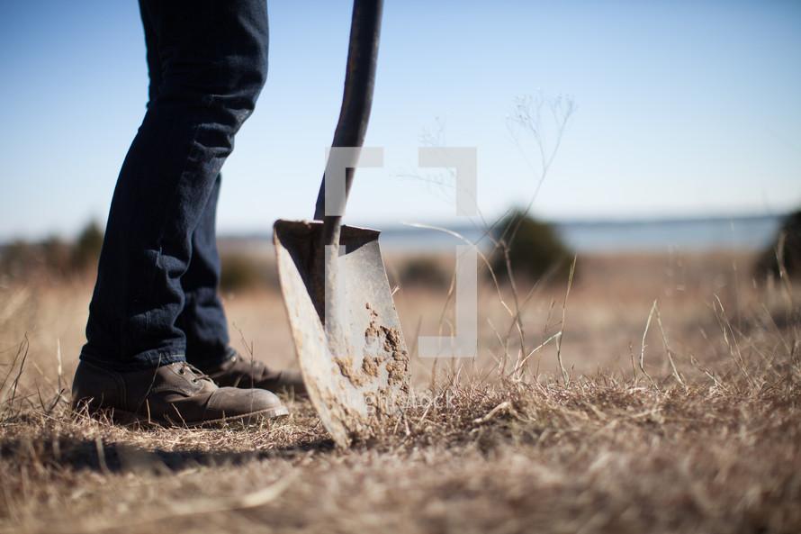 man standing next to a shovel