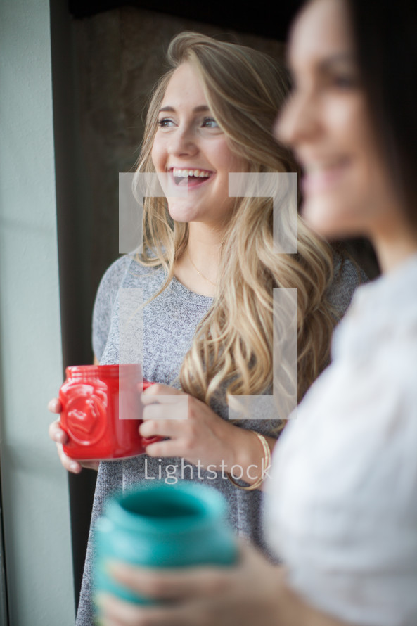 women in conversation drinking coffee at a window