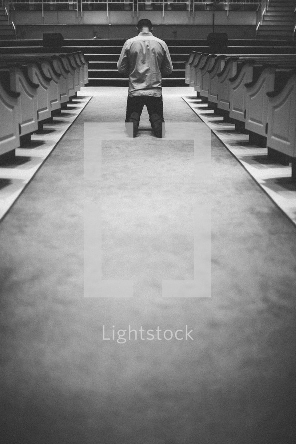 Man kneeling with head bowed in center aisle.