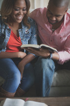 couple reading a Bible together on a couch