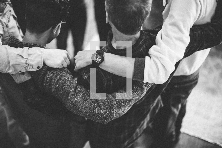 arms around each other in a prayer circle