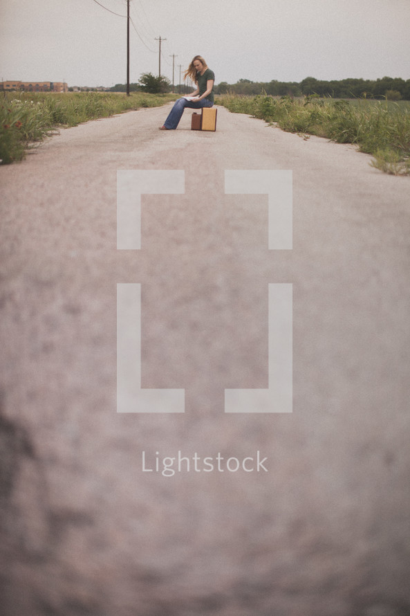 Woman sitting on a suitcase in the middle of a dirt road.