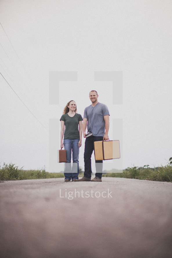 man and woman standing in the middle of a road carrying luggage