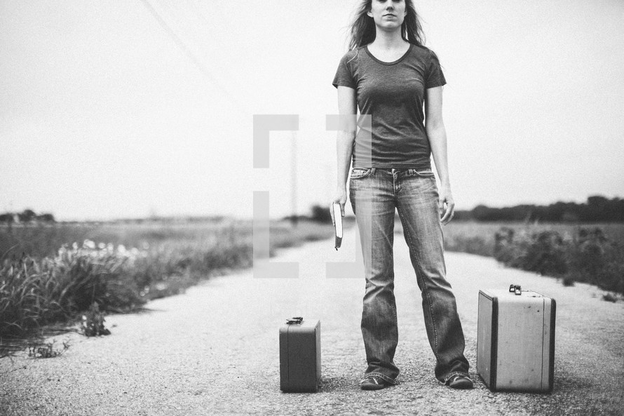 woman standing in the middle of a road next to luggage holding a Bible