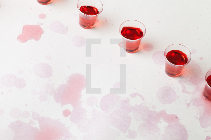spilled red wine in communion cups