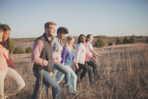 group of people walking through a field