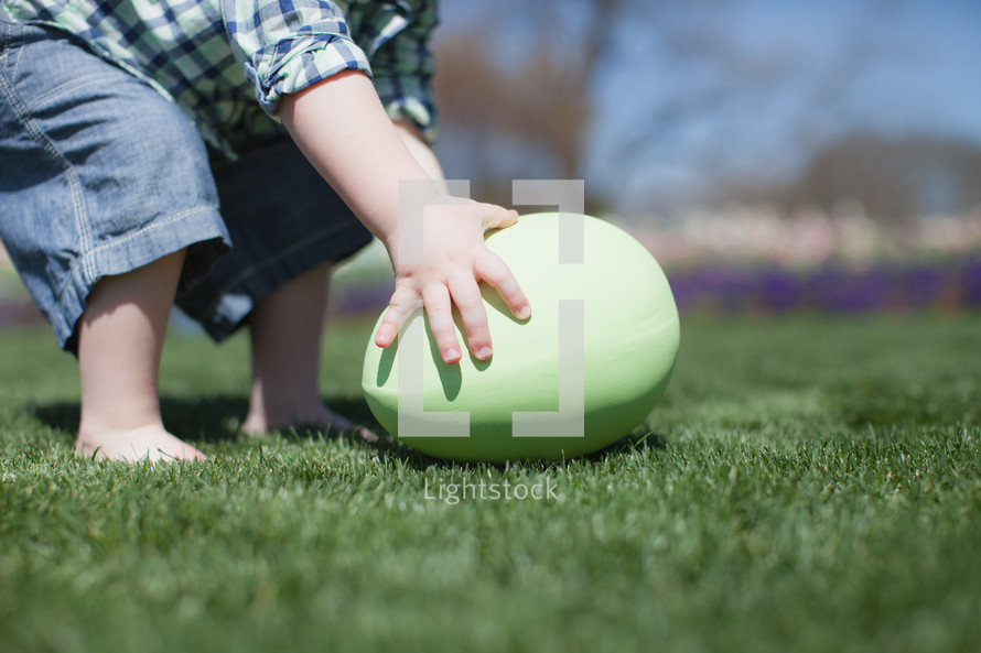 Child reaching down for a giant Easter egg in the grass.