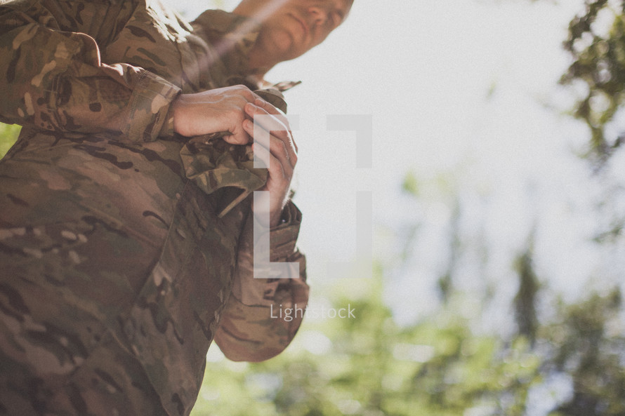 serviceman praying holding his hat