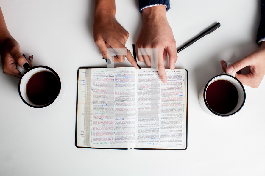 looking down at an open Bible and coffee mugs at a Bible study