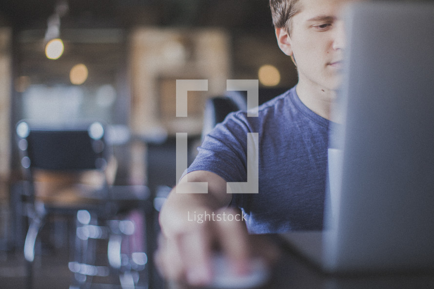 man working at his laptop in a coffee shop