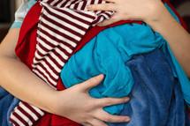a woman holding dirty clothes