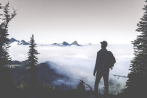 man standing on a mountain top in fog and clouds looking out at Mt Rainer