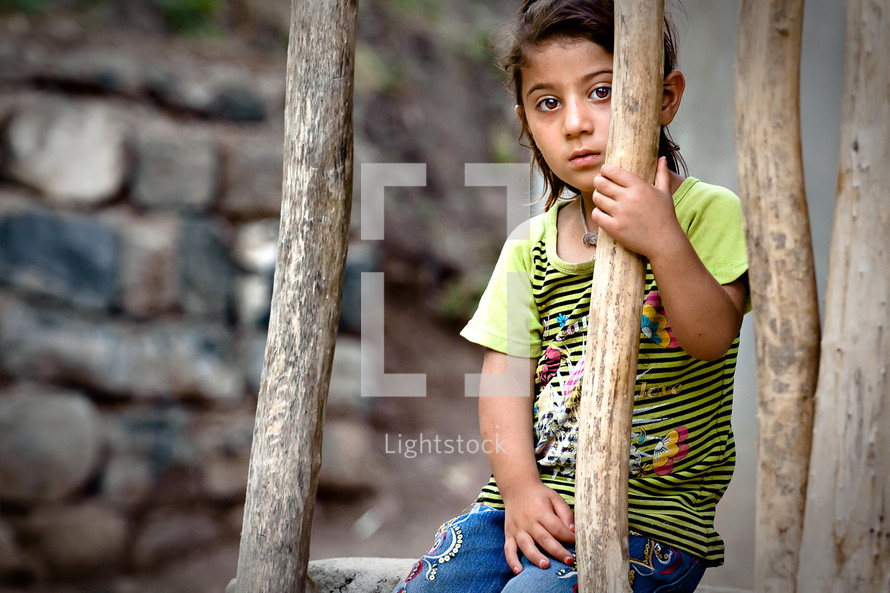 Young girl sitting behind wooden branches