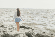 girl standing on a rocky shore looking up to God