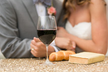 torso of a bride and groom and communion bread and wine