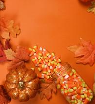 candy corn in a mason jar on an orange background