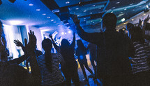 crowd with hands raised at a worship service