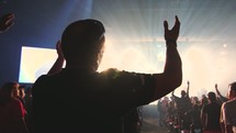 audience with raised hands in worship at a concert
