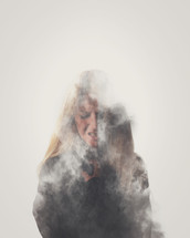 silhouette of a woman behind smoke