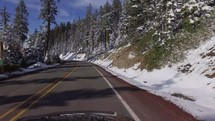 driving down a road lined by snowy hills