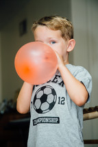 a boy child blowing up a balloon