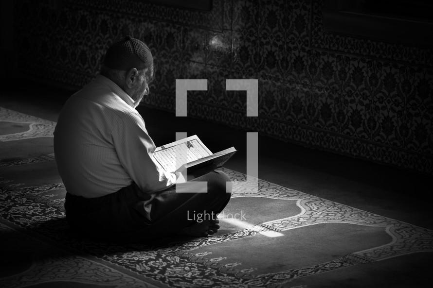 Elderly muslim man reading book