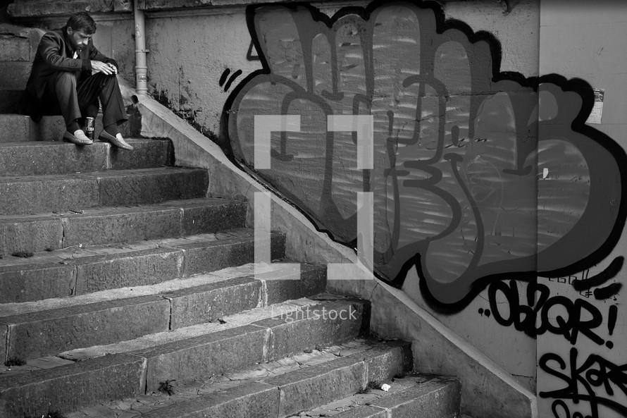 Man on concrete steps near graffiti wall