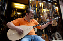 Turkish man playing Saz outside music store