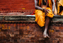 A man sitting on a brick wall wearing traditional clothing