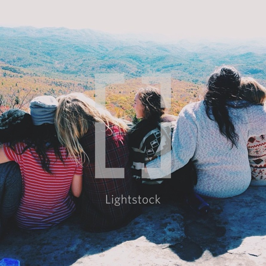 A group of girls sit closely together on a rock ledge.