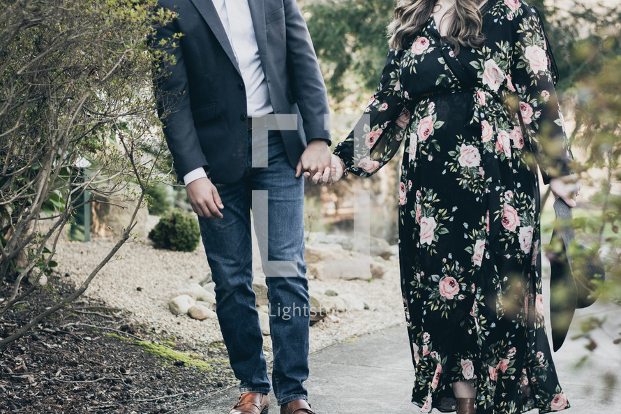 a couple expecting a baby holding hands