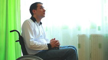 Young man in wheelchair praying