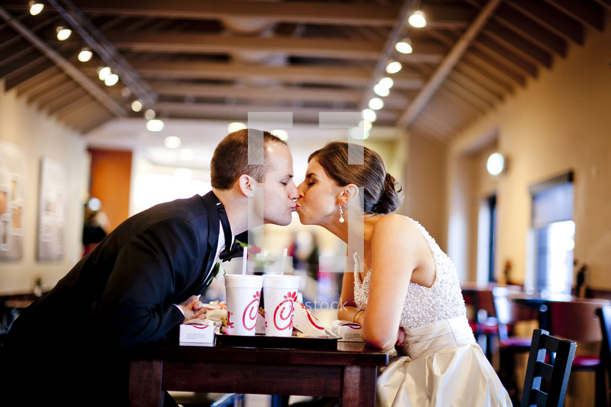 Bride and groom eating at fastfood restaurant