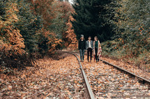 friends standing in the middle of train tracks