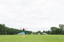 a woman standing in a field with raised hands