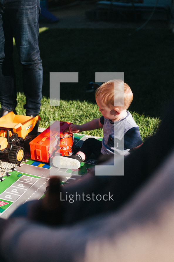 a child playing with toy cars outdoors