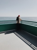 man standing on a pier looking out at the water below