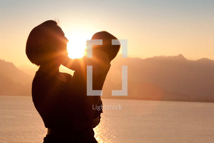 toddler boy with his hands on mother's face at sunset