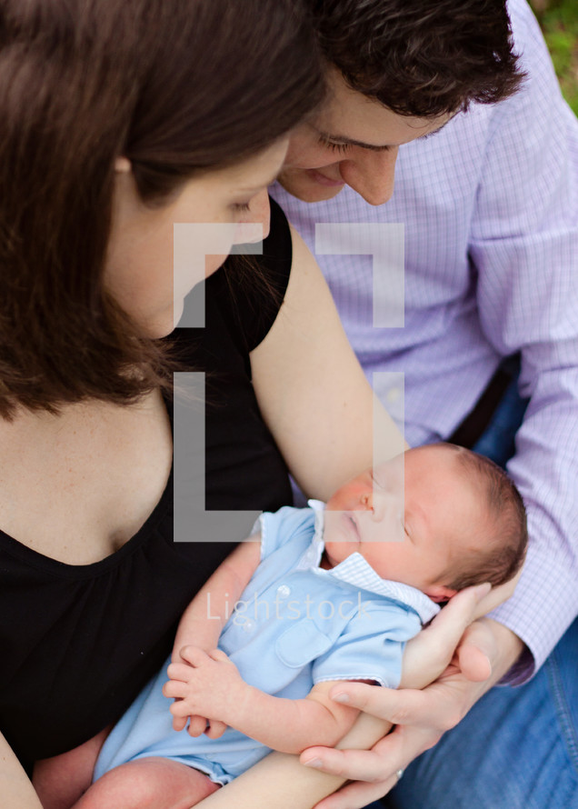 mother and father holding their newborn son