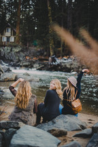 women looking across a river at a cabin