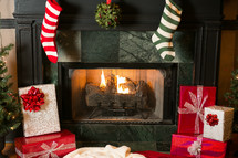 stockings and mistletoe hanging on a hearth and wrapped presents