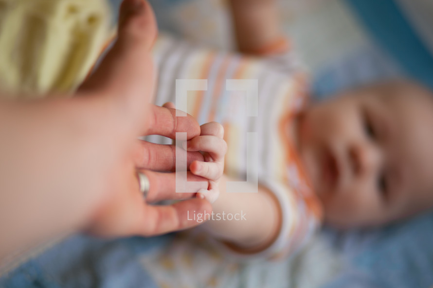 parent and infant holding hands