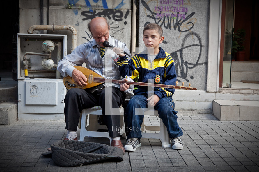 man and boy street musicians playing a sax