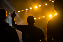 silhouettes of raised hands during a worship service