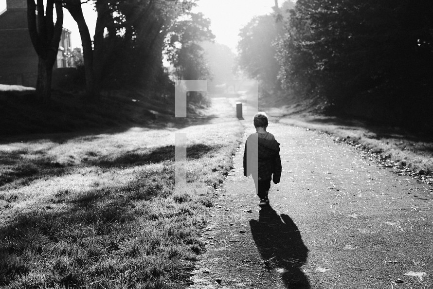 toddler walking on a trail in a park under rays of sunlight