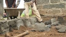 unloading rocks from a wheelbarrow in Kenya